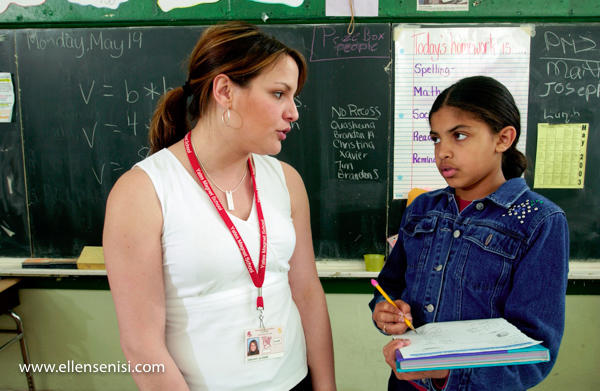 Teacher talking with student in classroom
