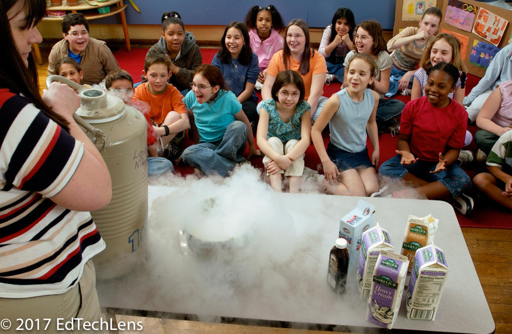 Excited fourth-grade students watch as scientist mom demonstrates qualities of liquid nitrogen to her daughter's class.