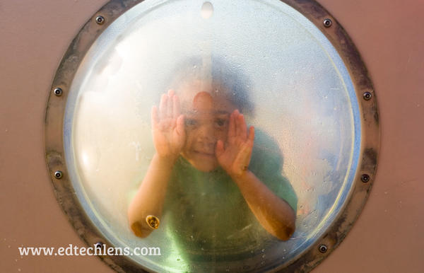 The importance of play: child peeking out of round window on play equipment
