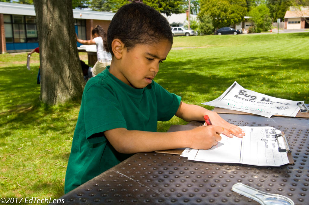 Kindergarten boy writes notes for his science record book after a class bug hunt