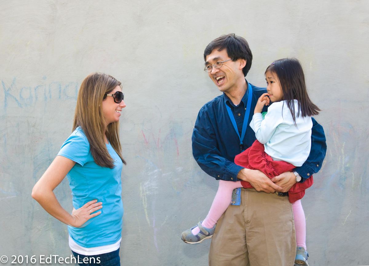 Father holding his daughter and teacher talk at end of school day