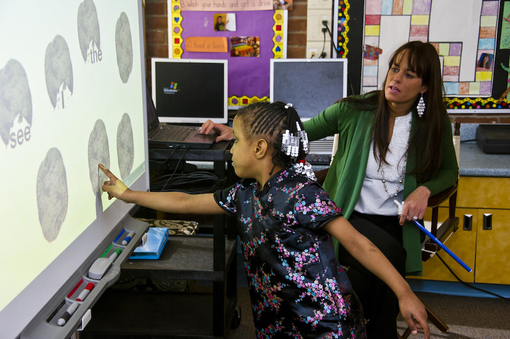 Kindergarten teacher guides student using sight-word recognition software on digital display