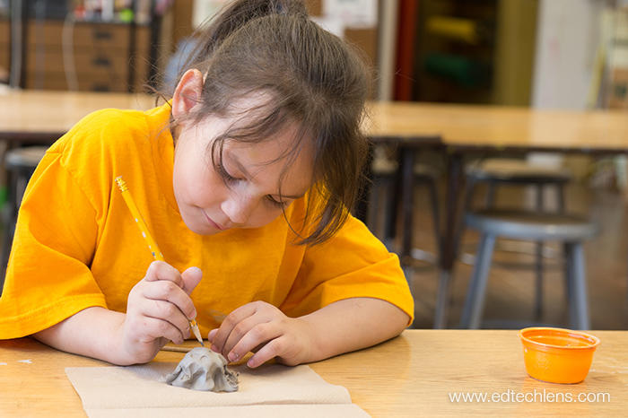 A kindergartner at a school with a Rainforest Journey subscription uses a pencil to make a pattern on the shell of her turtle in art class. The art lesson included scientific and art concepts, and students also learned how to use clay and clay tools to make their turtles.