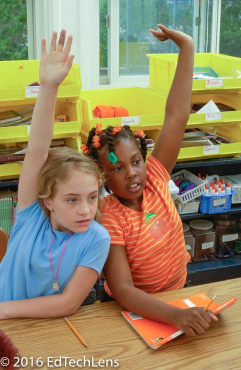 Two third-grade girls raise hands to answer teacher's questions