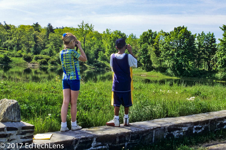 Two fifth-grade students photograph at a park near their school for a long-term project that involves documenting changes in the landscape throughout the seasons.